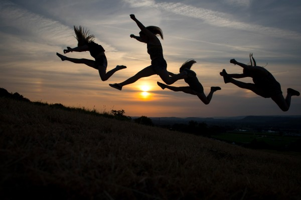 GLASTONBURY, ENGLAND - JUNE 20: Festival goers jump in the air as they pose for a photograph as people gather to watch the sun set ahead of the gates opening to the public amid heightened security this year at the Glastonbury Festival site at Worthy Farm in Pilton on June 20, 2017 near Glastonbury, England. The largest greenfield festival in the world Glastonbury Festival is now a five-day festival of contemporary performing arts. The Somerset Festival, which Michael Eavis started in 1970 when several hundred hippies paid just £1, now attracts more than 175,000 people. (Photo by Matt Cardy/Getty Images)
