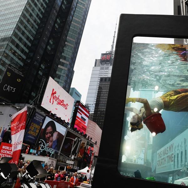 NEW YORK, NY - 31. Mai: Performance Künstlerin Annie Saunders performt in einem Wassertank auf dem Times Square  in New York (Credit: Getty Images)