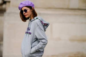 PARIS, FRANCE - SEPTEMBER 27:  A guest wears a purple beret hat, a gray hoodie, a purple pleated skirt, purple shoes, sunglasses, outside Margiela, during Paris Fashion Week Womenswear Spring/Summer 2018, on September 27, 2017 in Paris, France.  (Photo by Edward Berthelot/Getty Images)