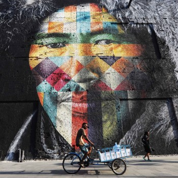 RIO DE JANEIRO, BRAZIL - MAY 31:  A man bikes past street art created by Eduardo Kobra decorating a building in the Port District, an area revamped ahead of the Rio 2016 Olympic Games, on May 31, 2017 in Rio de Janeiro, Brazil. While the Rio 2016 Olympic Games are generally regarded as having left Rio with a mixed legacy at best, an abundance of street art has flourished in the citys renovated Port District.  (Photo by Mario Tama/Getty Images)