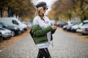 BERLIN, GERMANY - OCTOBER 24: Larissa Laudenberger wearing black pants Topshop, green down feather jacket Topshopt, black Zara flat cap, sungllases, grey Zara sweater, white Zara sock boots on October 24, 2017 in Berlin, Germany. (Photo by Christian Vierig/Getty Images)
